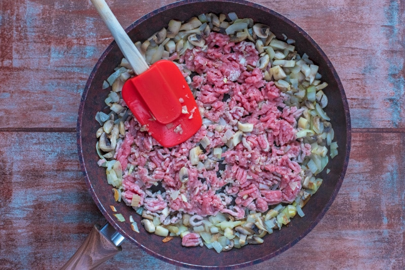 Chopped onion, mushrooms, ground turkey and garlic in a frying pan