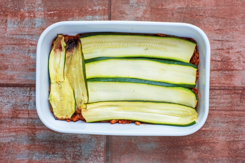 A baking dish containing a tomato meat sauce and strips of cooked zucchini