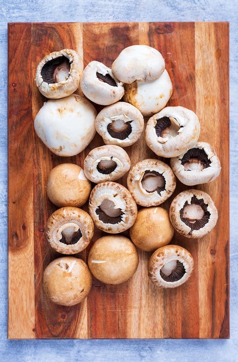 A wooden chopping board with a selection of mushrooms on it