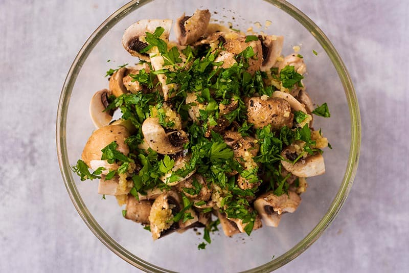 A glass bowl full of quartered mushrooms and chopped herbs