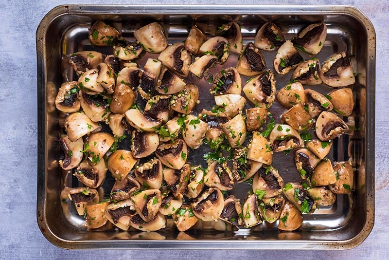 A baking tray covered in chopped mushrooms and herbs