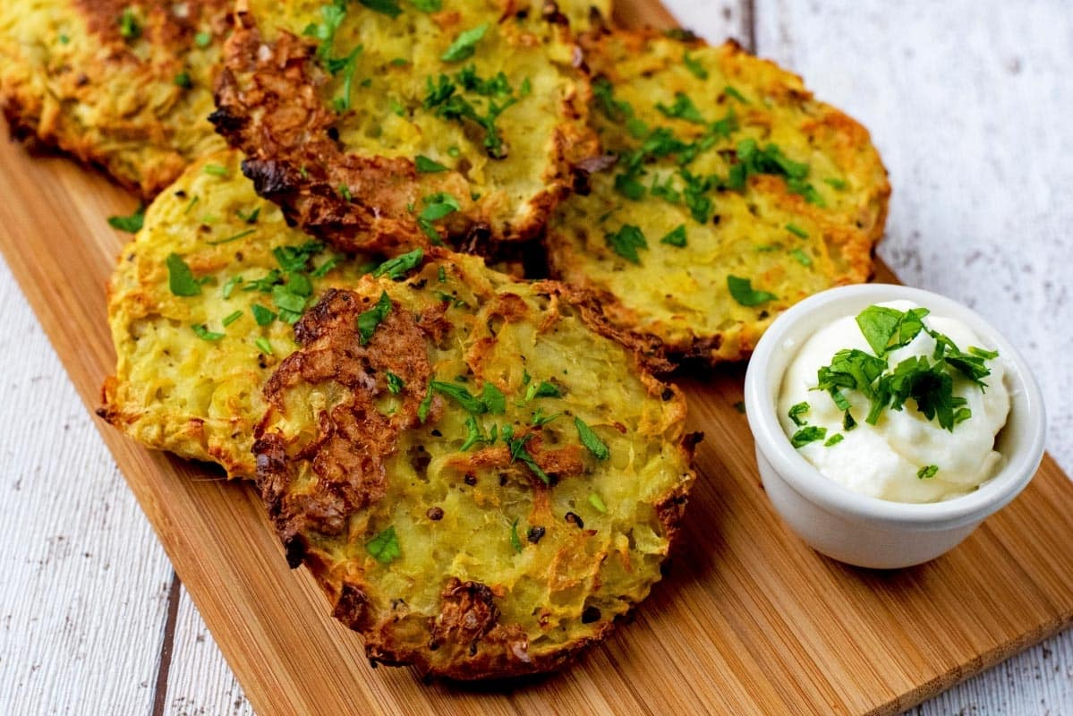 Oven baked hash browns on a wooden board with a small pot of dip