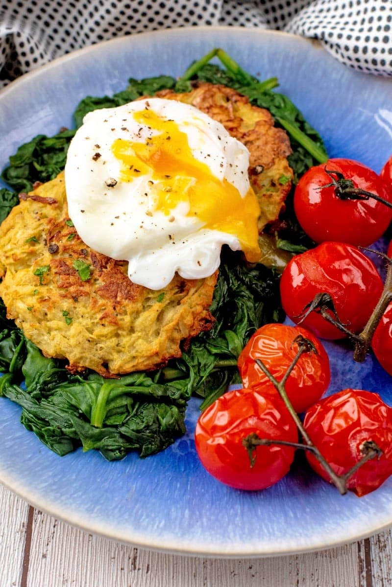 Oven Baked Hash Browns with a poached egg, spinach and cherry tomatoes, all on a blue plate