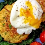 A poached egg, yolk running out, on top of two baked hash browns. Roasted tomatoes next to them