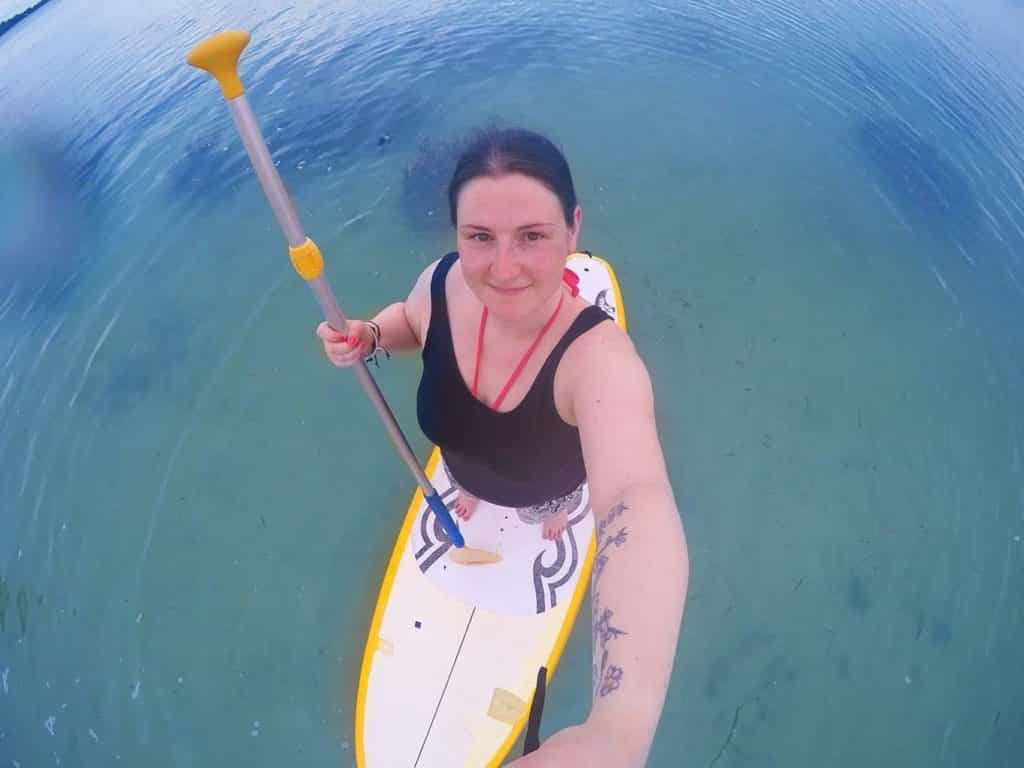 A woman taking a selfie while stood on a Paddle Board