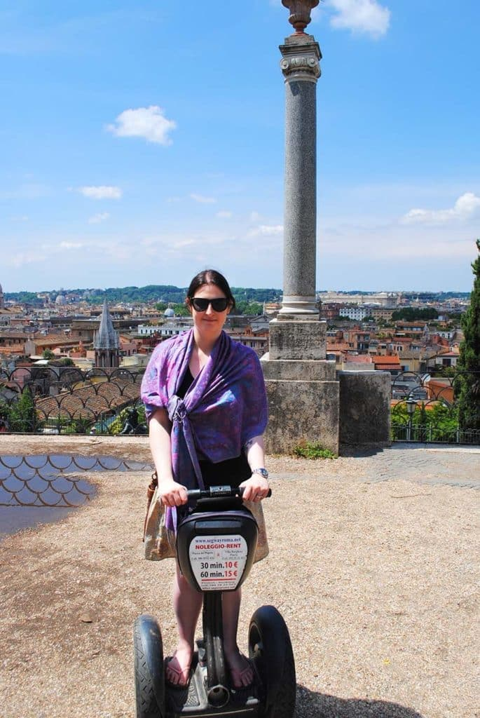 A woman riding a Segway with a city skyline in the background