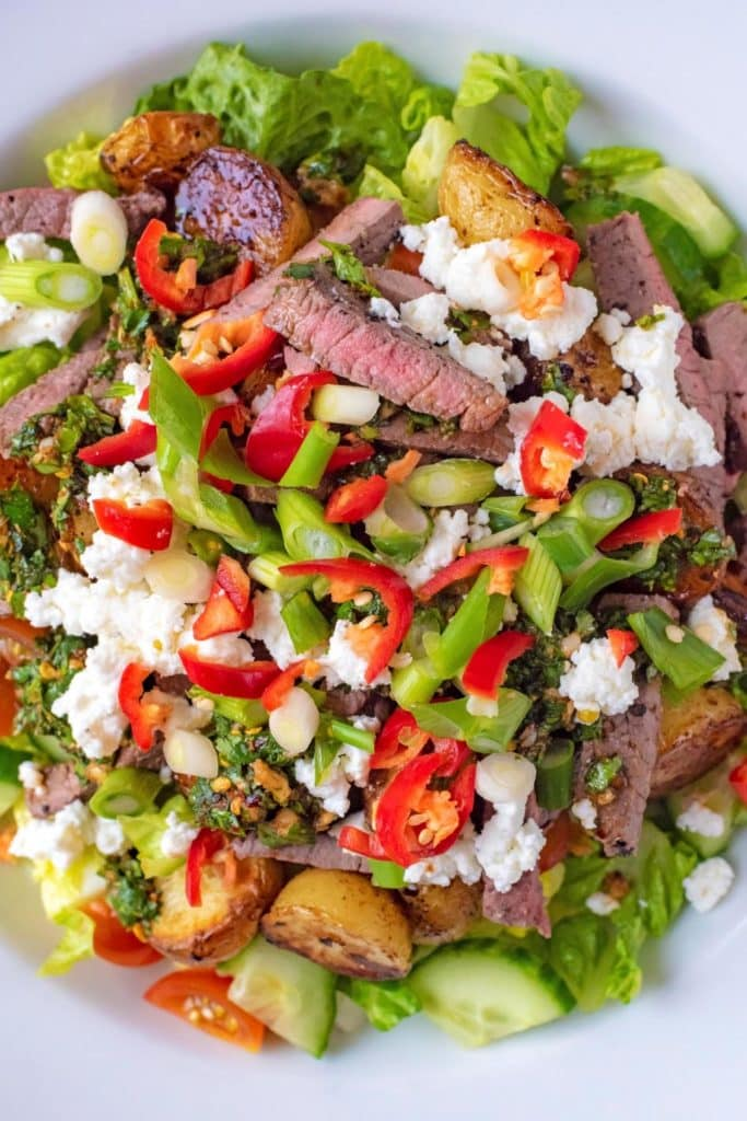 Salad leaves topped with sliced steak, cheese and chillies