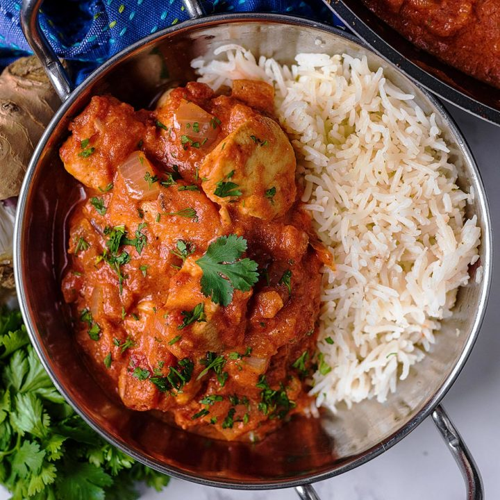 Murgh Makhani Butter Chicekn in a metal dish with white rice