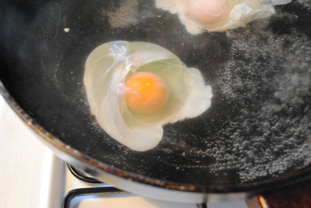 eggs poaching in a frying pan