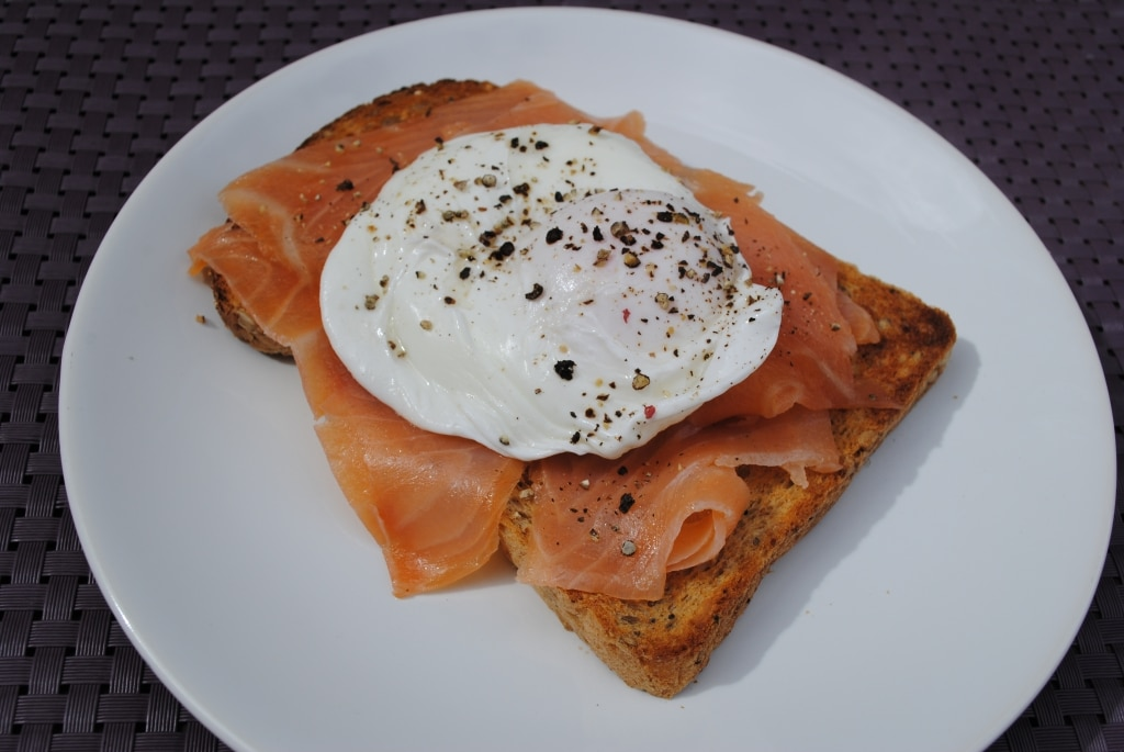 a poached egg on some smoked salmon on toast