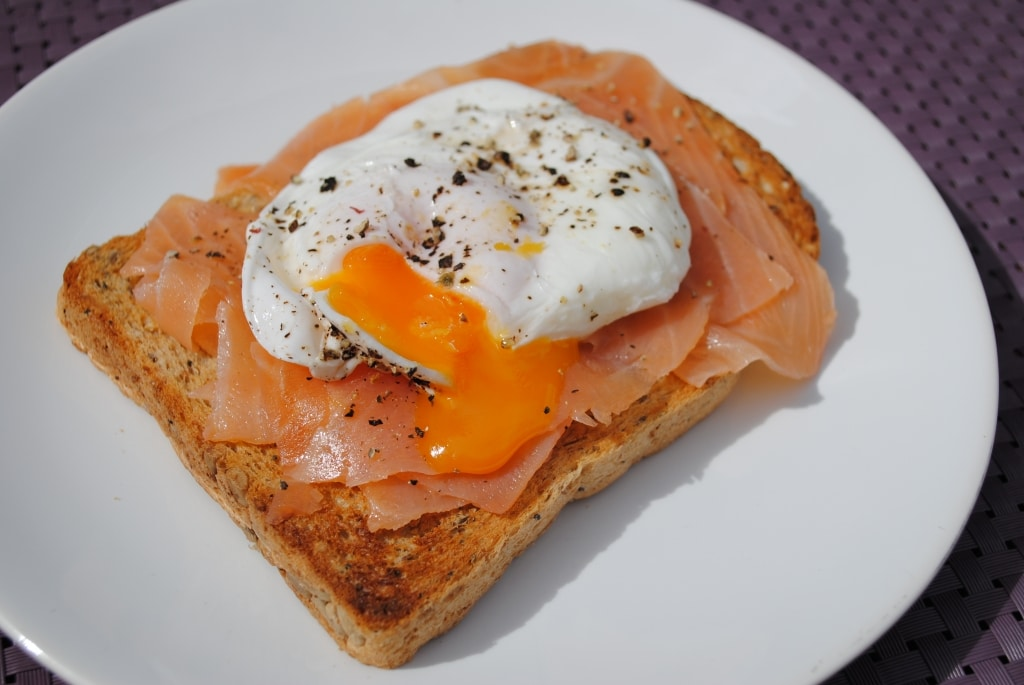 A poached egg with the yolk running out onto some smoked salmon on toast