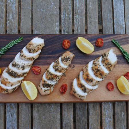 Sliced lemon rosemary chicken on a wooden serving board