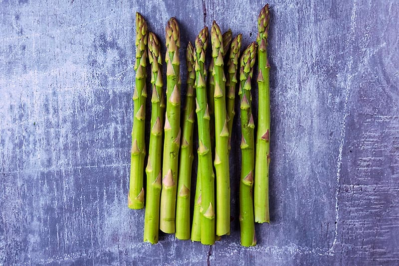 Ten asparagus spears on a wooden surface