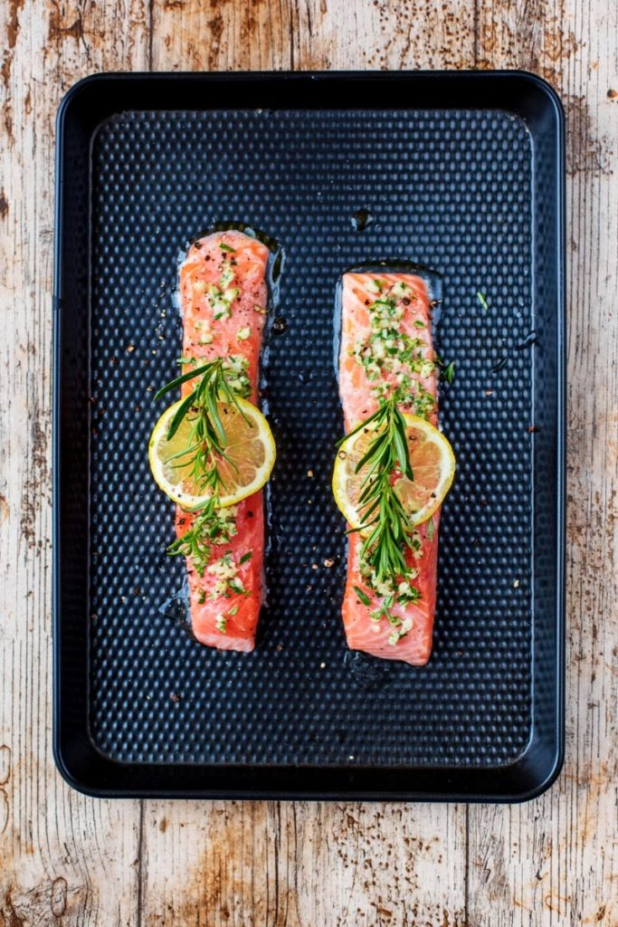 Two salmon fillets on a baking tray with lemon and rosemary
