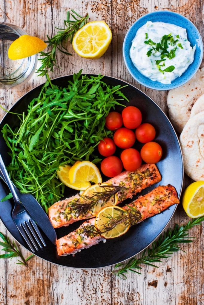Lemon and Rosemary Salmon on a black plate with tomatoes and salad