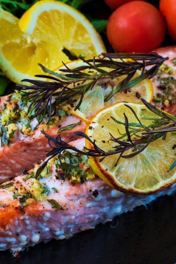 Rosemary sprigs and lemon slices on top of two salmon fillets