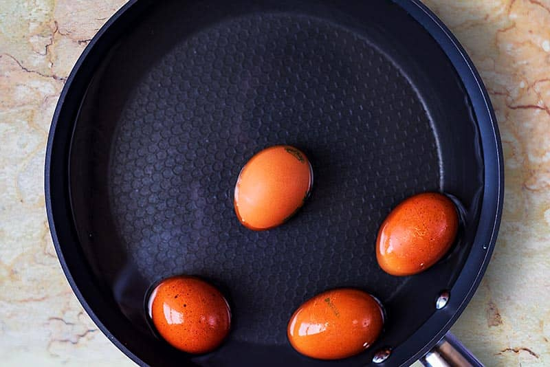 A frying pan full of water with four whole eggs in it