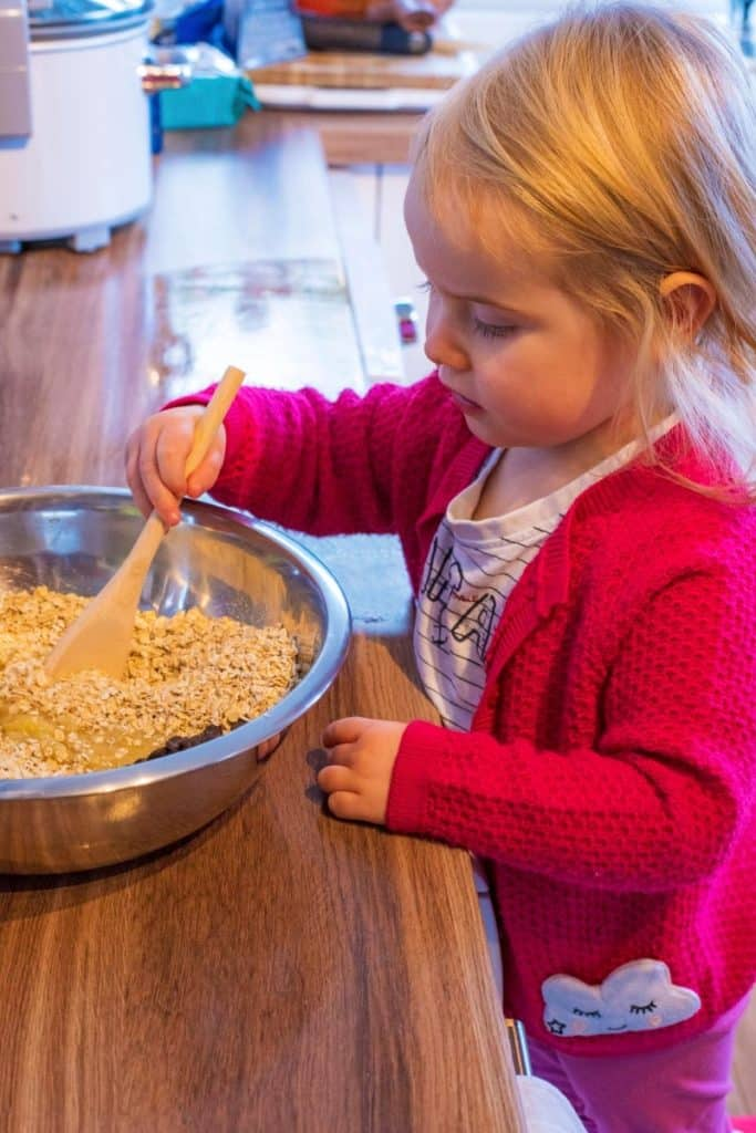 A young child mixing cookie ingredients in a bowl