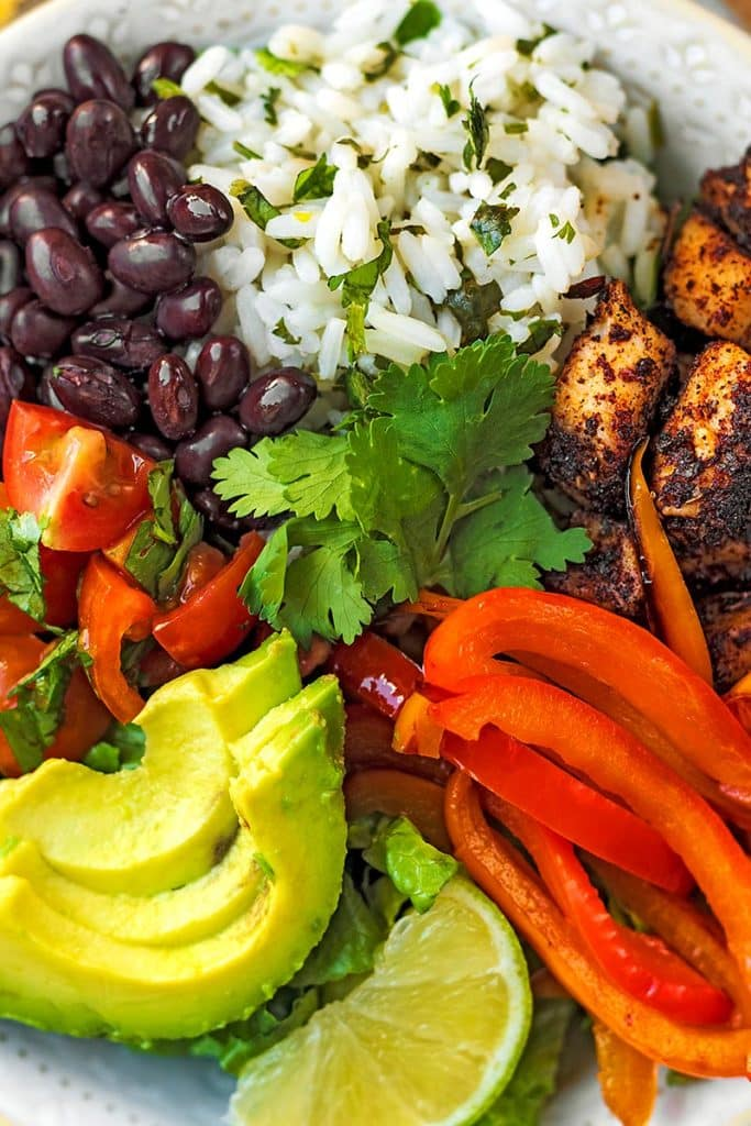 Sliced avocado, chopped tomatoes, black beans, cooked rice, seasoned chicken chunks, sliced red pepper and a lime wedge, all in a bowl together