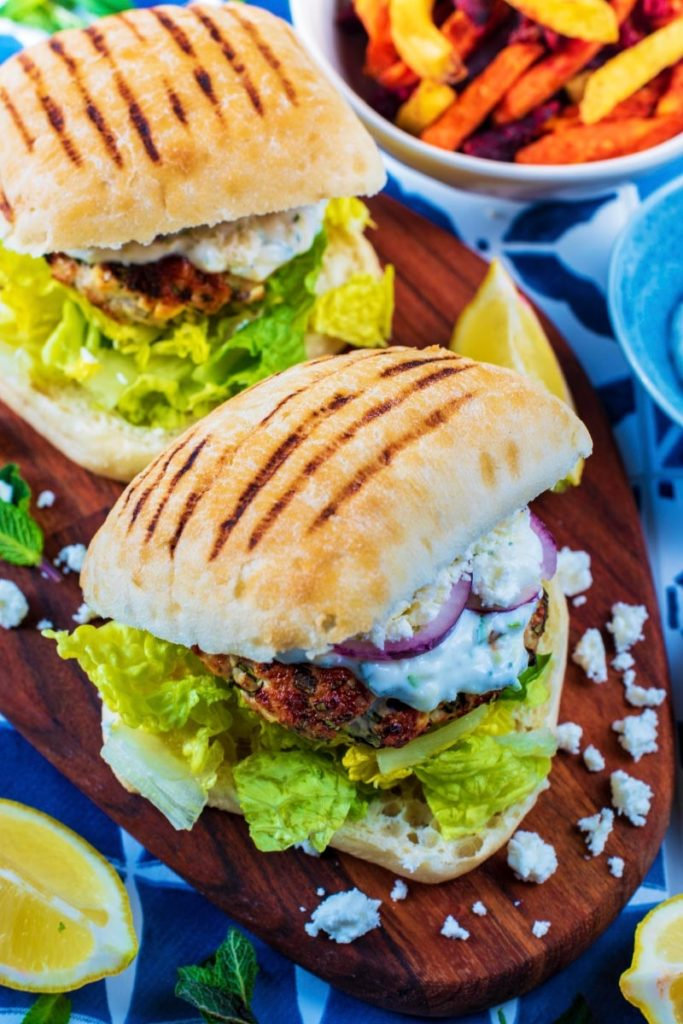 Two Greek Turkey Burgers surounded by crumbled feta