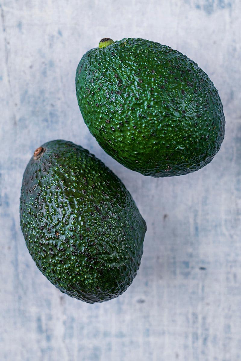 Two whole avocados on a wooden surface