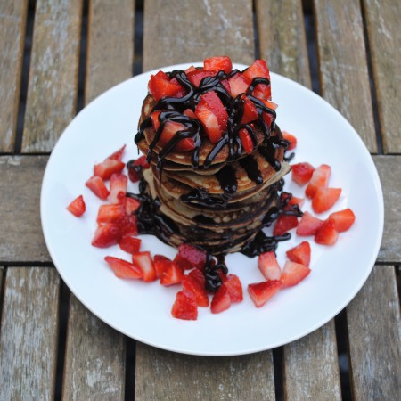 A stack of coconut pancakes topped with strawberries and chocolate sauce