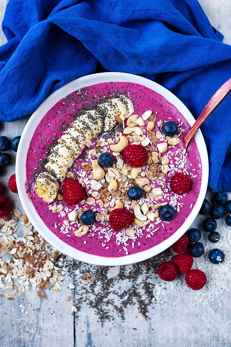 A purple smoothie in a bowl topped with fruit, nuts and seeds