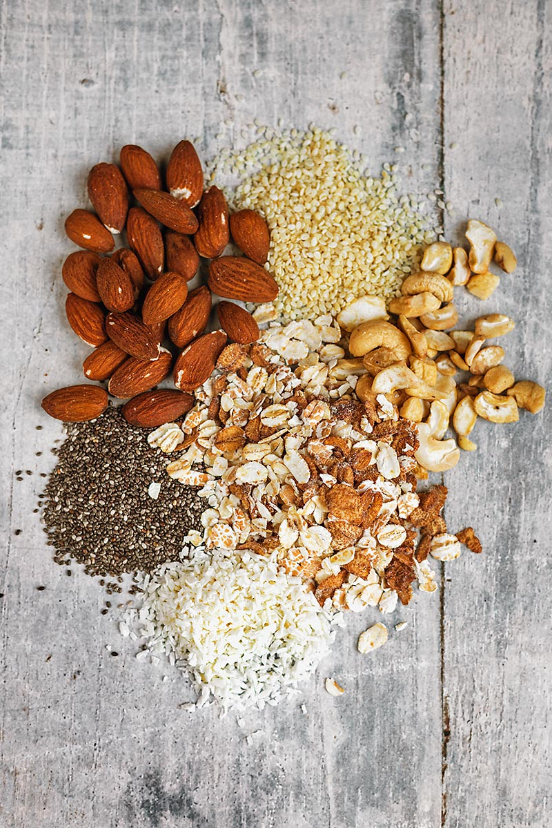 A selection of oats, nuts and seeds on a wooden surface