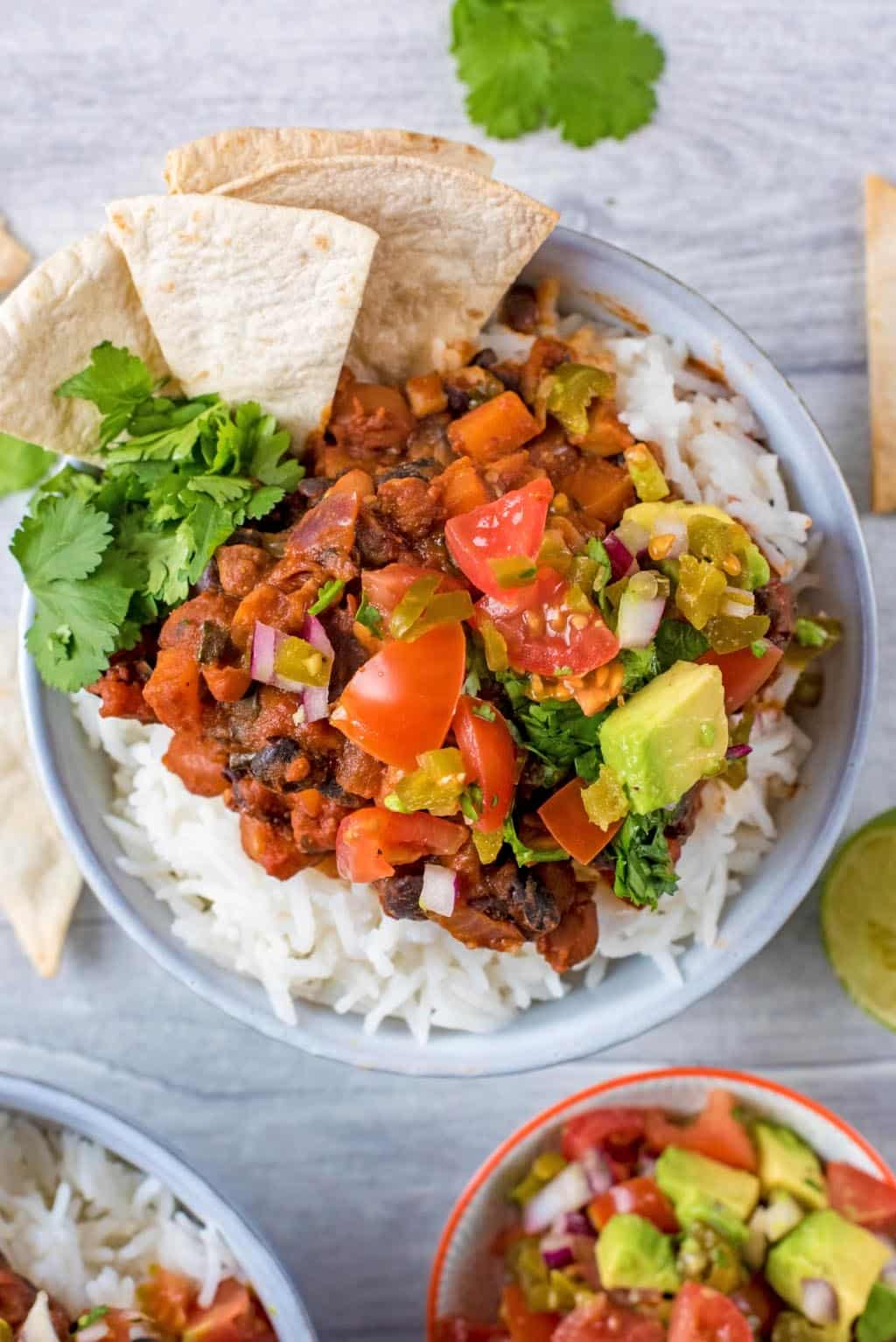 Bean Chilli and rice in a bowl topped with avocado salsa