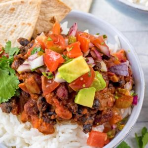 Bean Chilli on a bed of rice topped with salsa and avocado