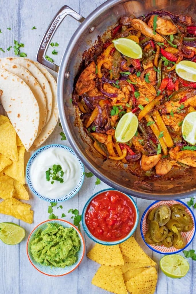 Oven Baked Chicken Fajitas in a large pan with fajita accompaniments
