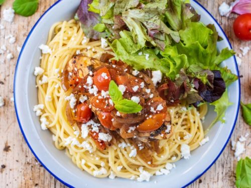 Slow Cooker Balsamic Chicken on a bed of spaghetti next to some salad leaves