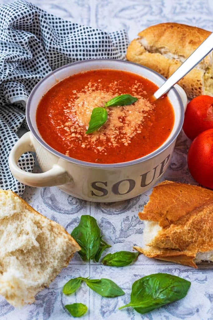 A bowl of tomato soup in a cream soup bowl. Bread and basil leaves are scattered around