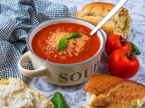 Tomato and Basil soup in a soup bowl next to bread and tomatoes