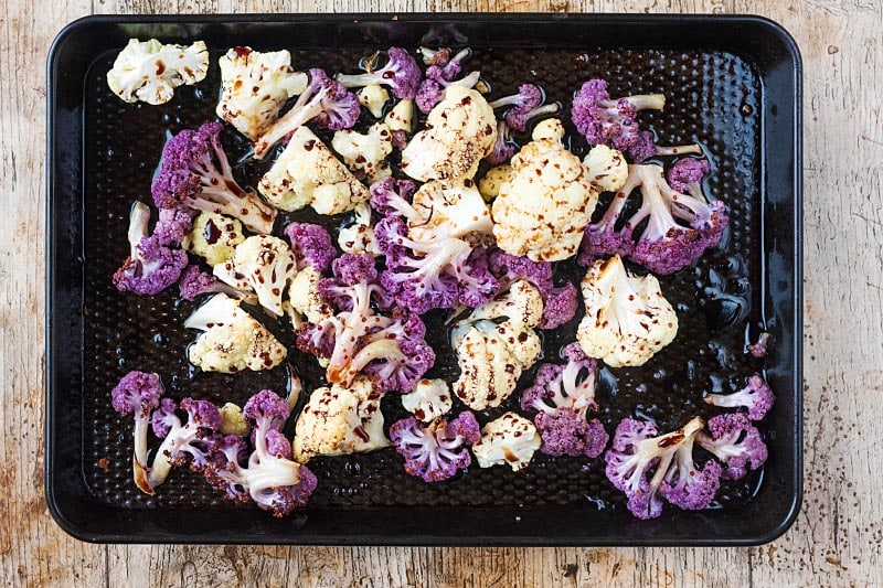 Cauliflower florets on a baking tray covered in oil, balsamic vinegar and seasoning
