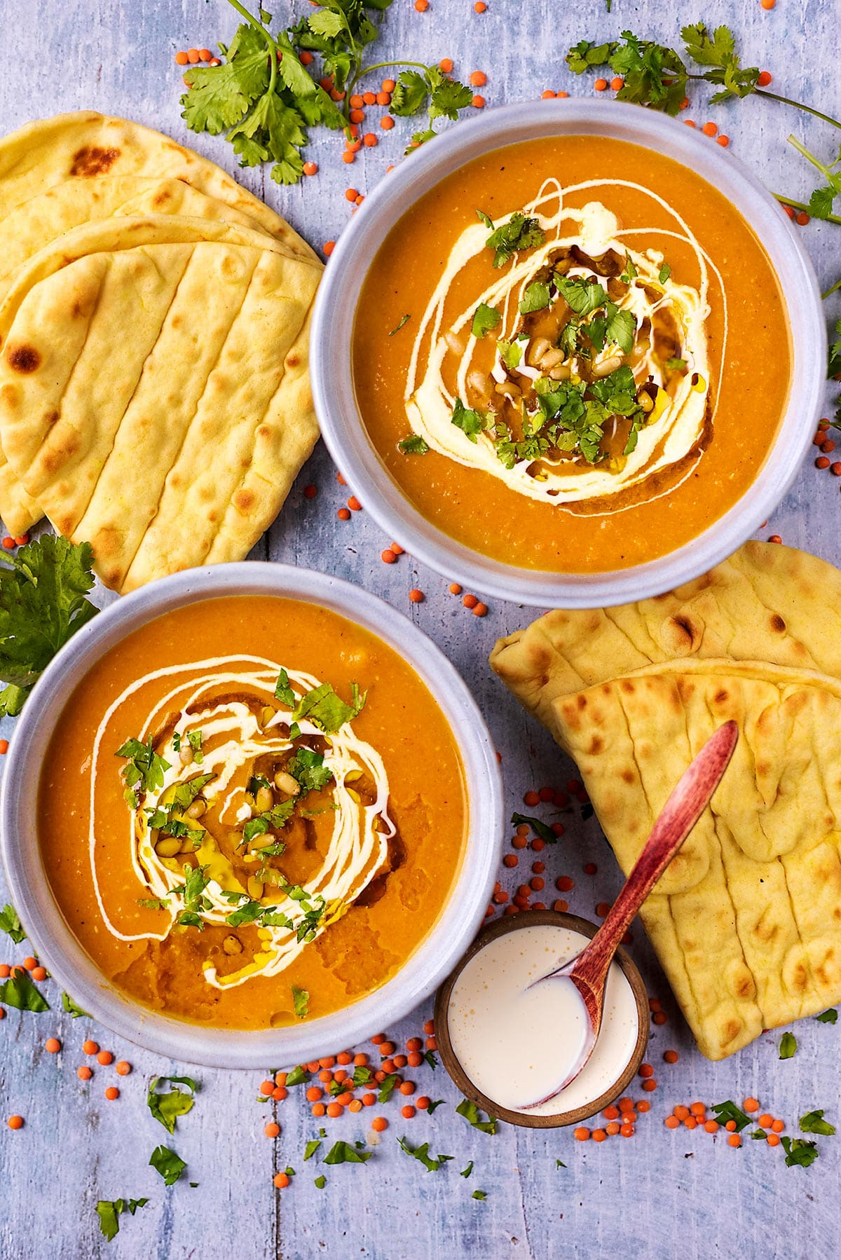 Two bowls of carrot and lentil soup next to some flatbreads and a small bowl of cream