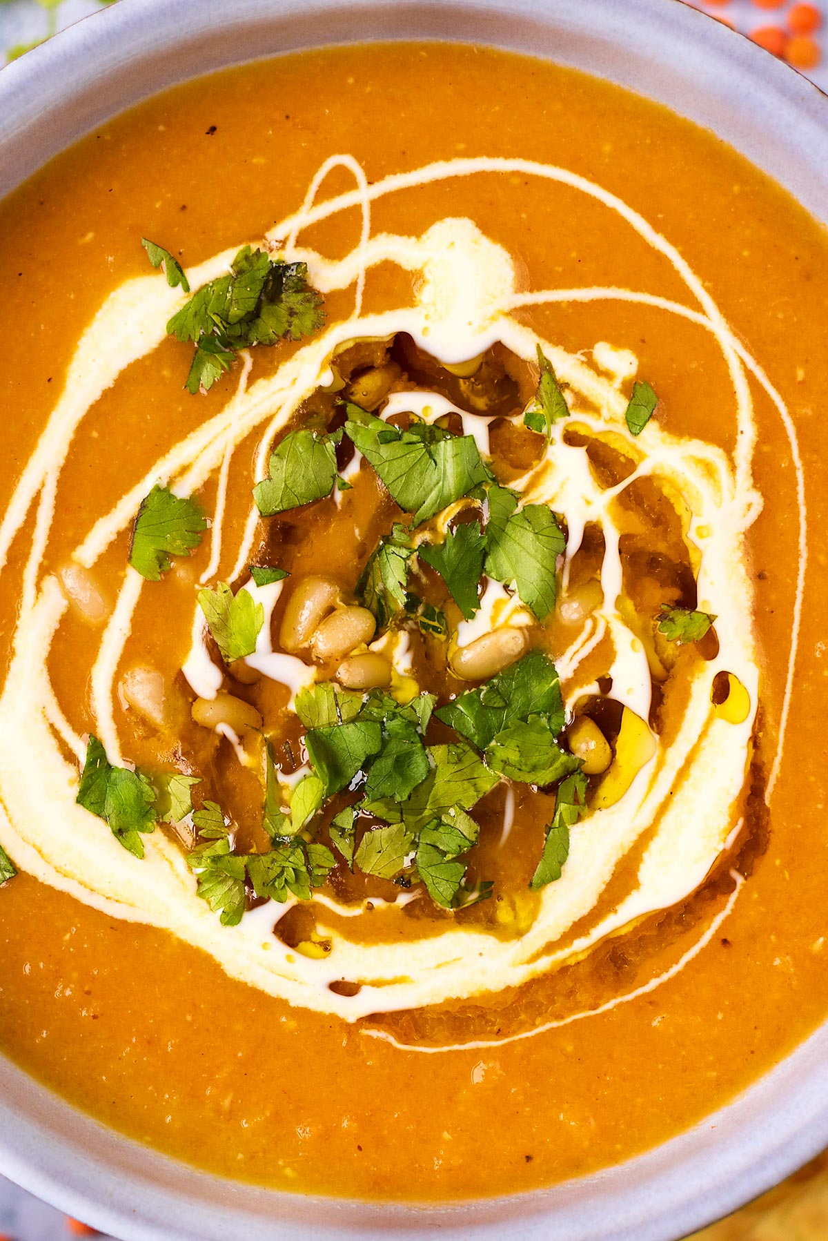 A bowl or red soup with a swirl of cream, some shopped herbs, a drizzle of oil and some pine nuts