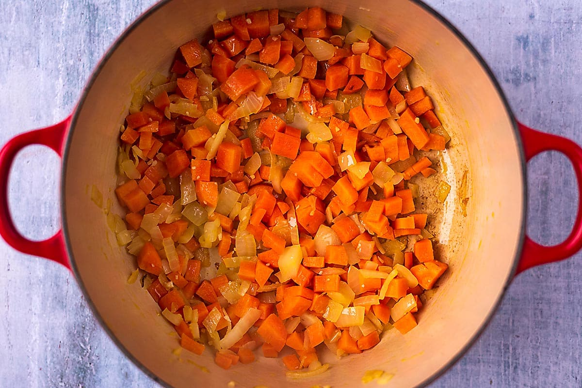 A large red pot with chopped carrots and onions cooking in it