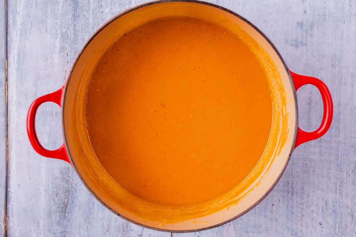 A blended red soup in a large cooking pot