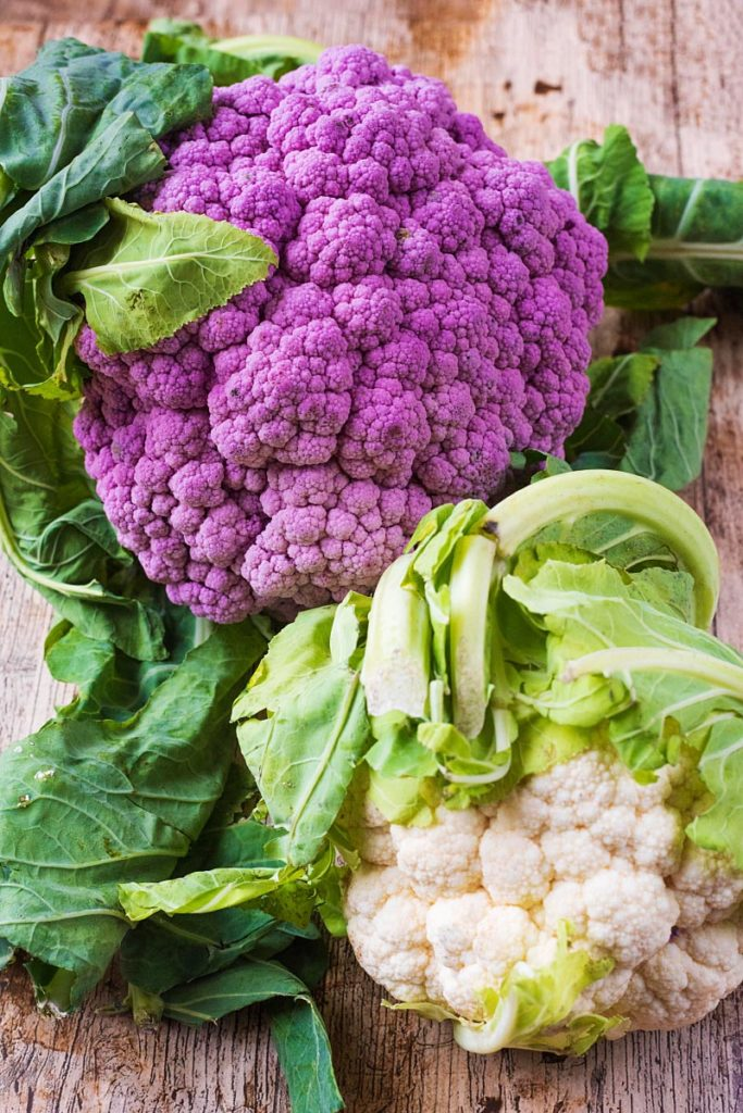 A whole white cauliflower and a whole purplu cauliflower on a wooden board