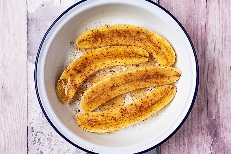 Four banana halves in a round dish covered in honey and cinnamon