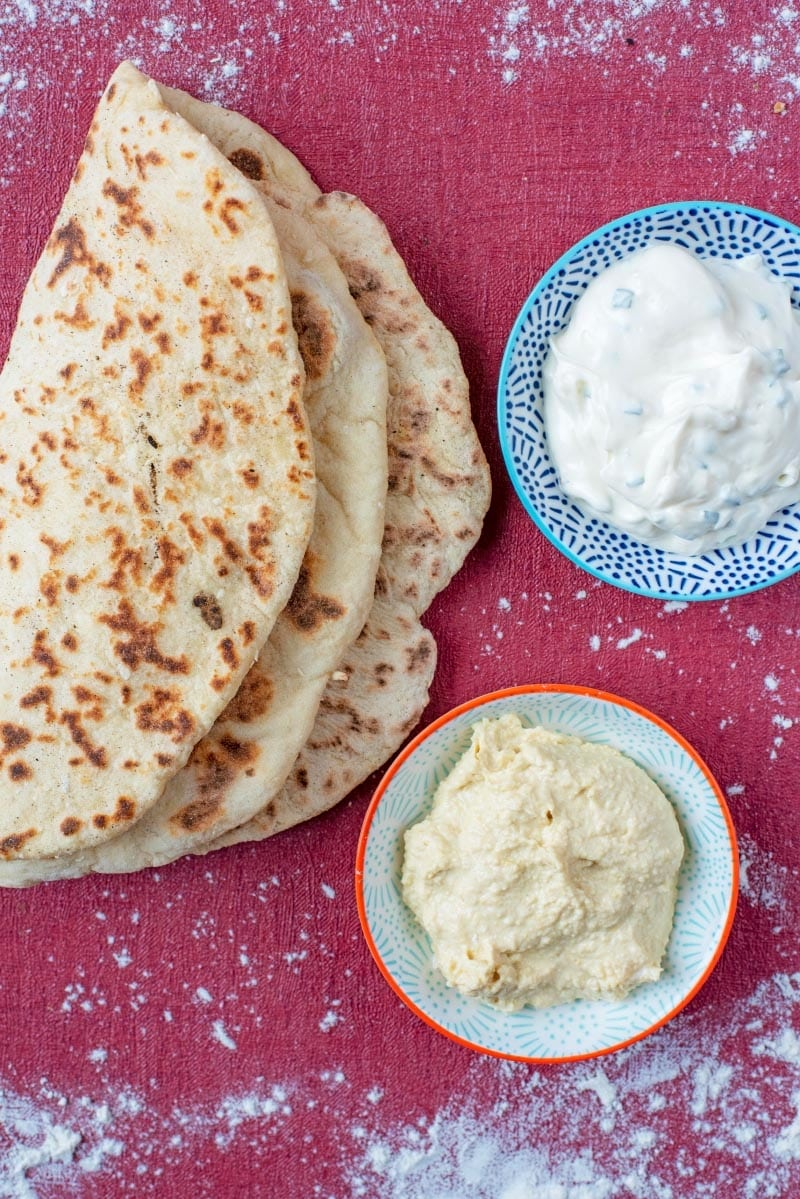 Folded flatbreads on a red surface with two bowls of dip