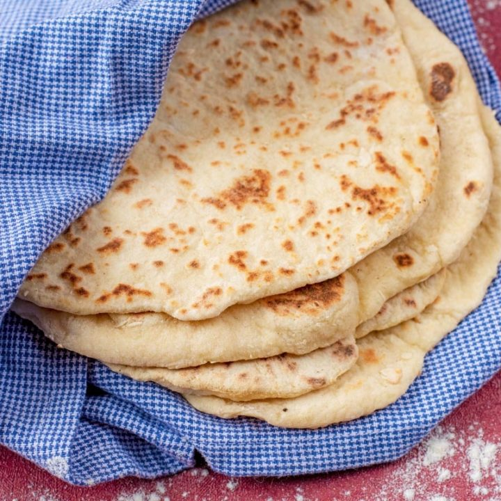 Easy Homemade Flatbreads wrapped in a blue gingham towel on a red surface. Flour is sprinkled around