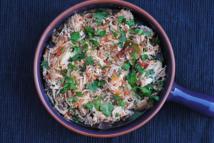 Shredded chicken in a dish topped with cilantro