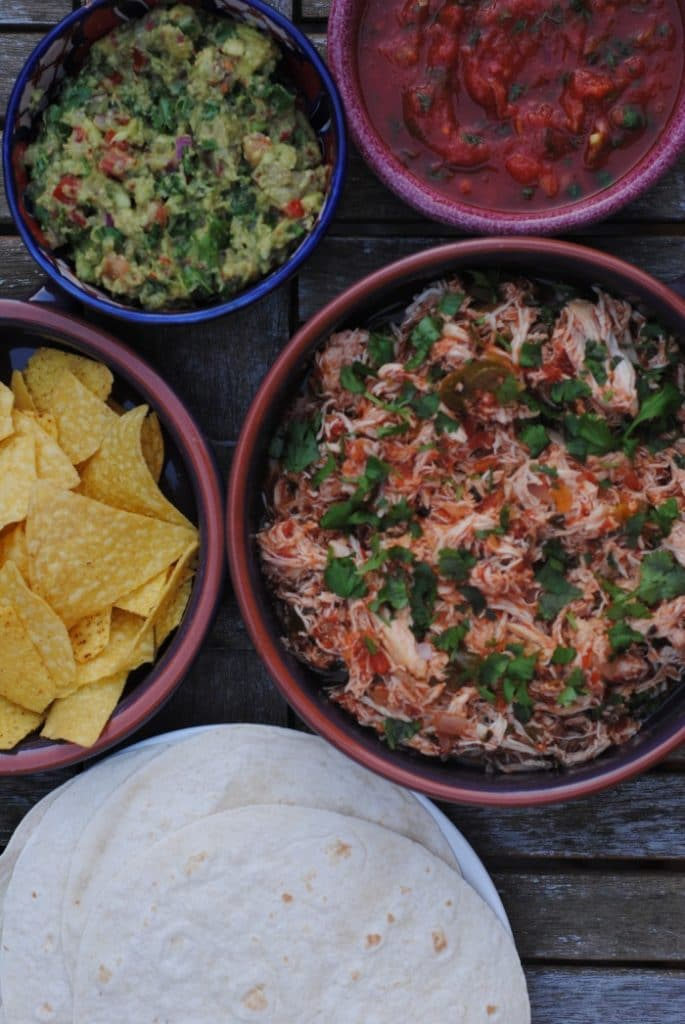 A bowl of shredded salsa chicken next to dishes of guacamole, salsa and tortillas
