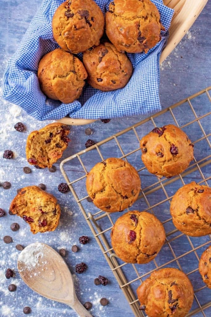 A basket of Cranberry Orange Muffins next to more muffins on a cooling rack