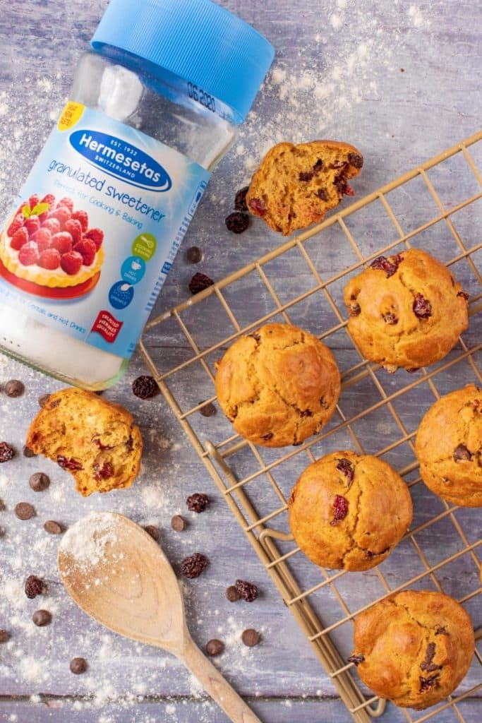 A jar of Hermesetas Granulates Sweetener next to muffins on a cooling rack