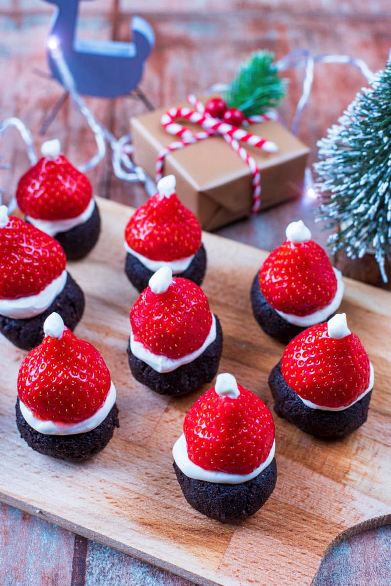 Santa Hat Brownies on a wooden serving board with Christmas decorations in the background