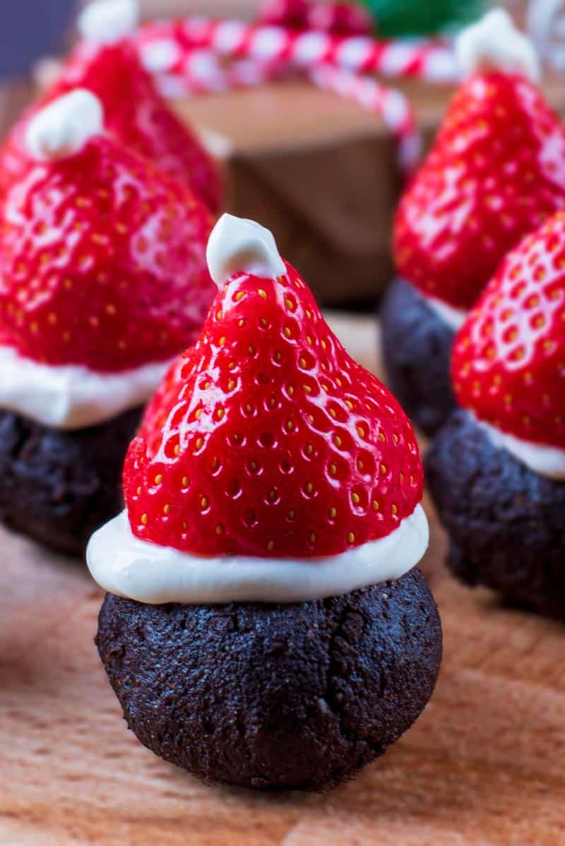 A raw chocolate brownie topped with a straberry to make it look like a Santa hat