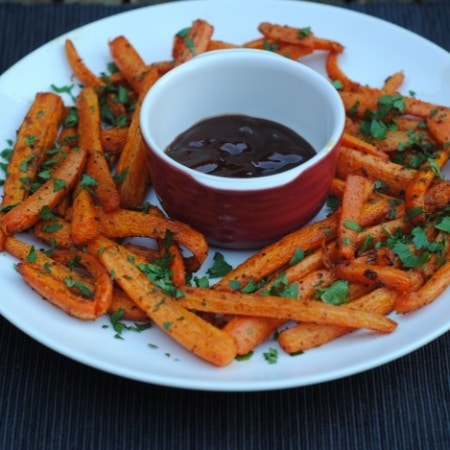 Baked carrot fries on a plate surrounding a pot of sauce